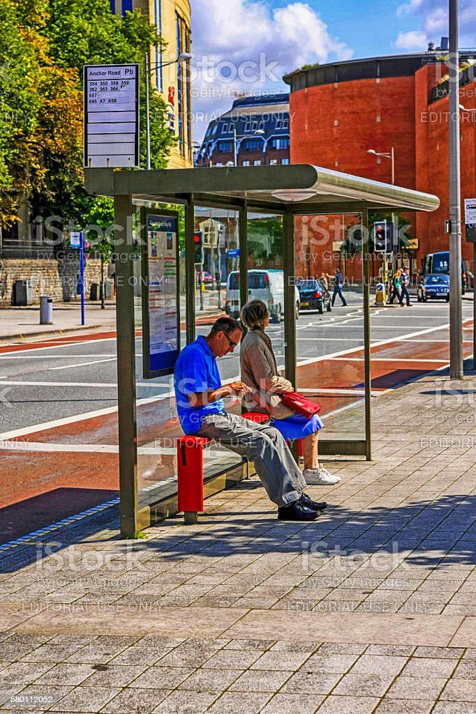 People waiting at a bus shelter in Bristol, UK stock photo