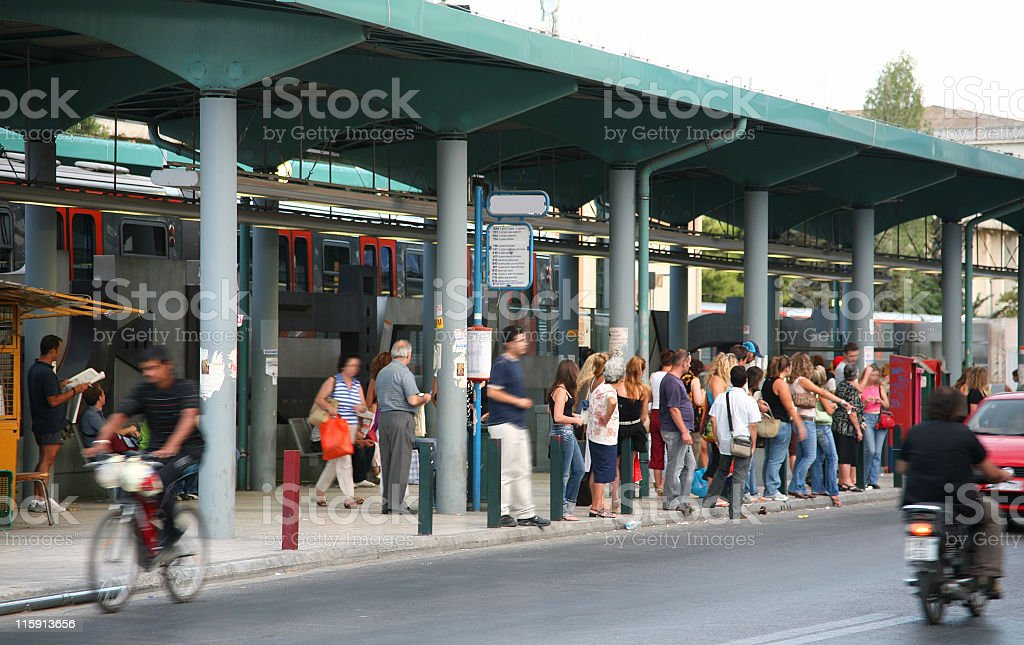 People waiting at a busy bus stop, with train in background royalty-free stock photo