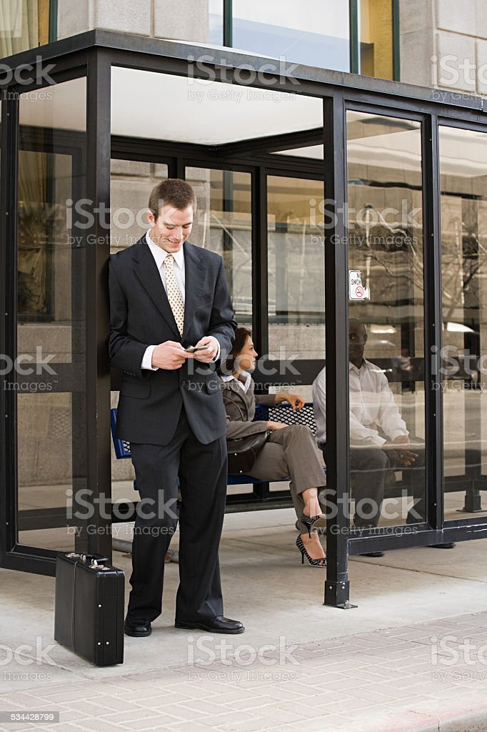 People waiting at bus stop stock photo