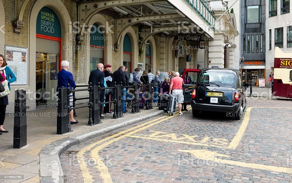 People waiting for taxis outside Charing Cross Station, London stock photo