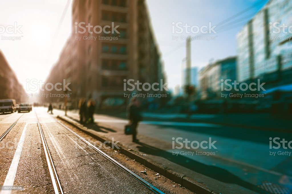 People waiting for tram on sidewalk outdoor in the city stock photo