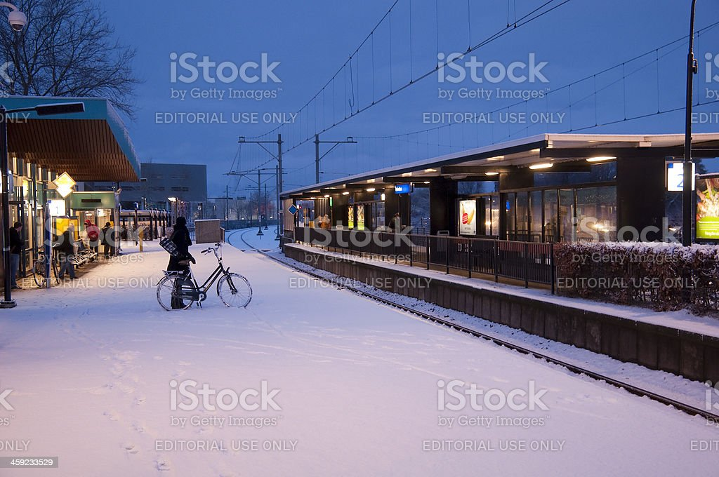 People waiting on an empty and snowy railway station stock photo