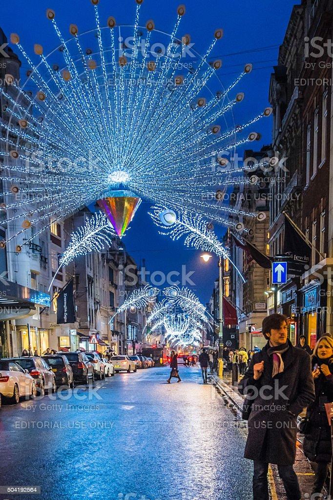 People walk along a beautifully illuminated New Bond Street, London stock photo