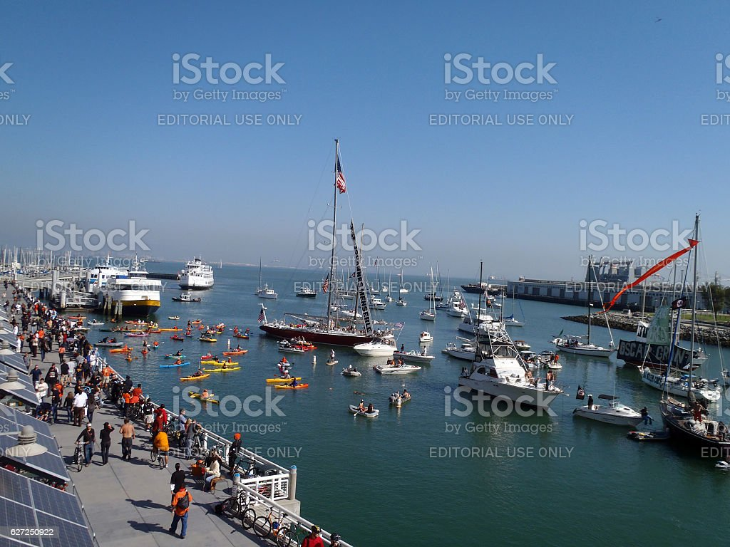 People walk along promenade with boats filling McCovey Cove stock photo