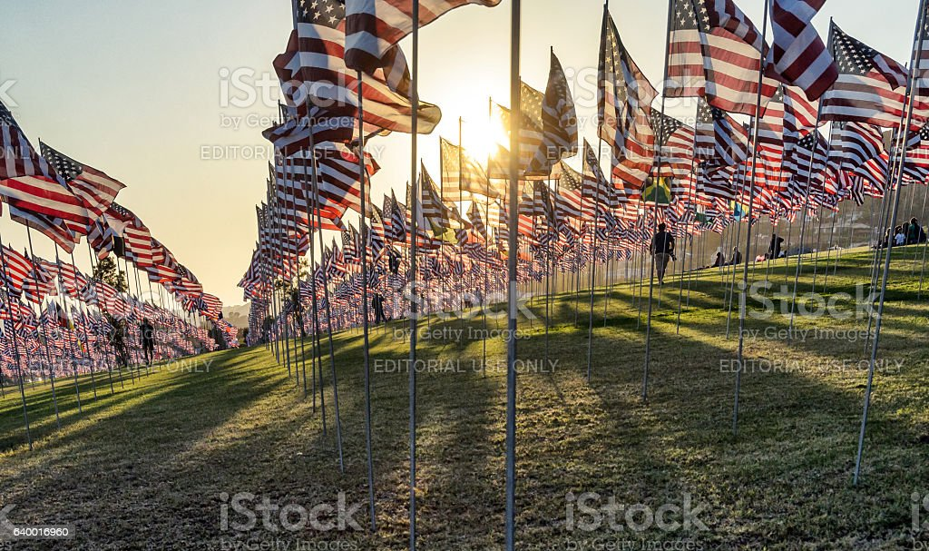 People walk among patriotic display of American flags stock photo