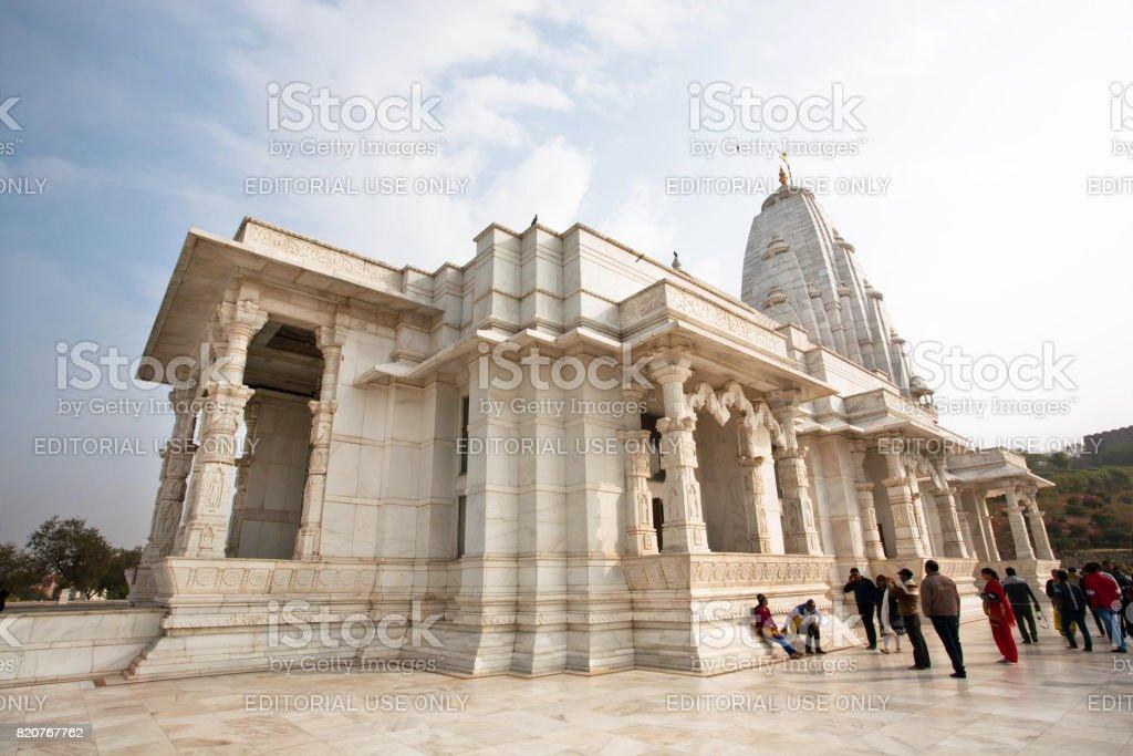 People walk around white marble Birla Temple, dedicated to Lords Vishnu and Lakshmi stock photo