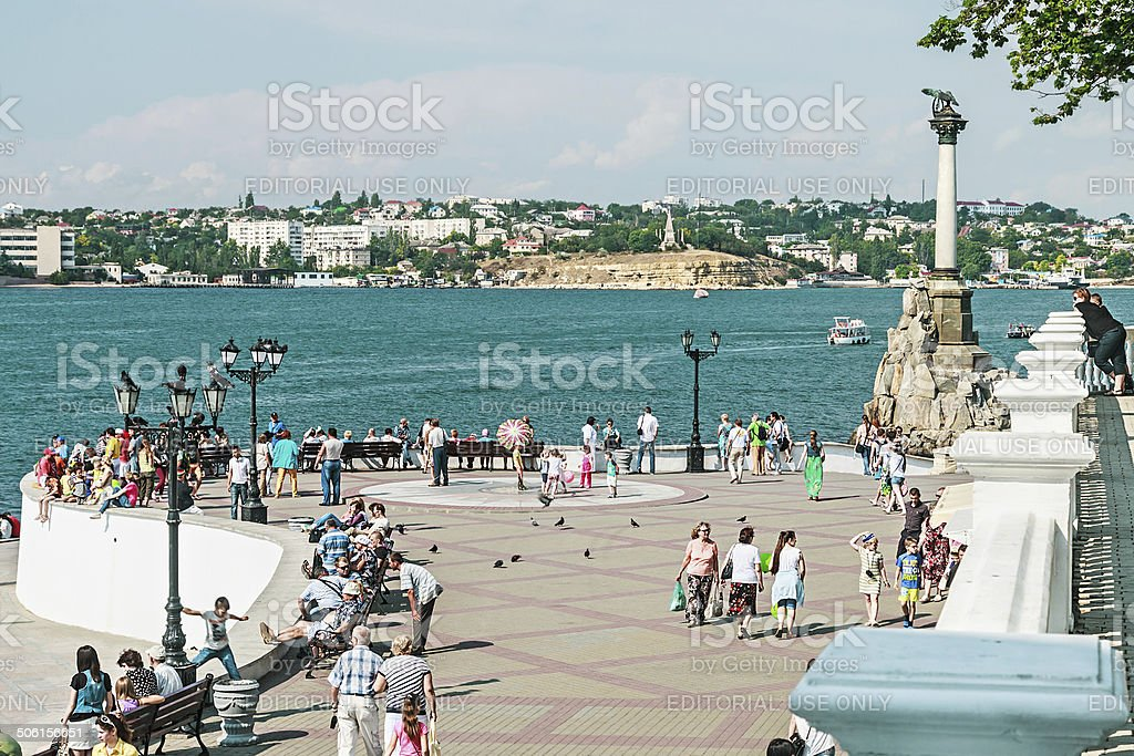 people walk at embankment near the Monument of dead ships stock photo