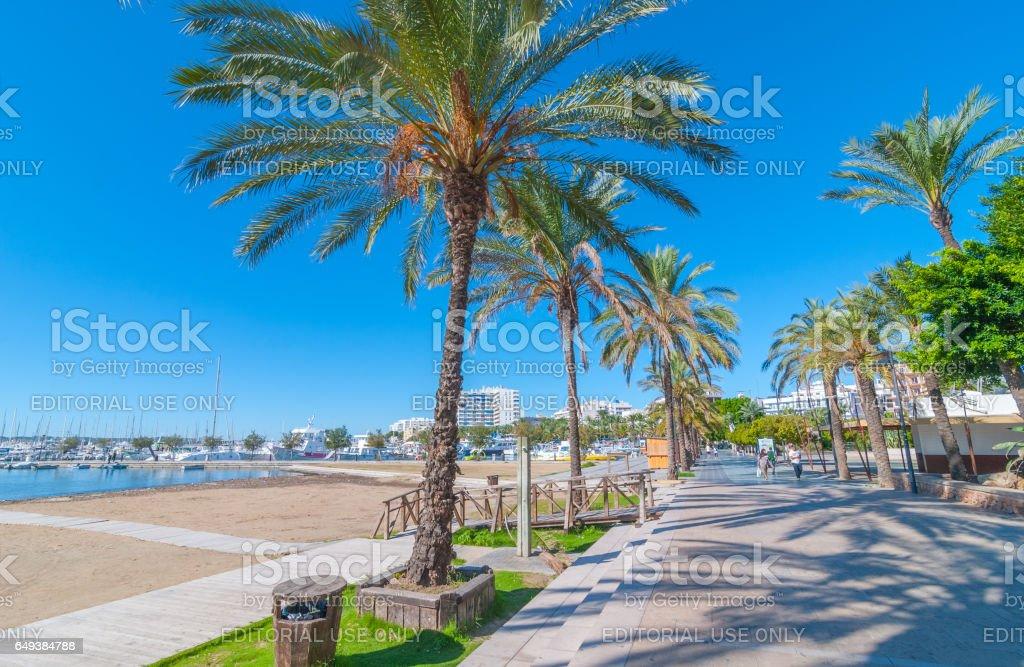 People walk beside the beach in Sant Antoni de Portmany, Ibiza, Spain. stock photo