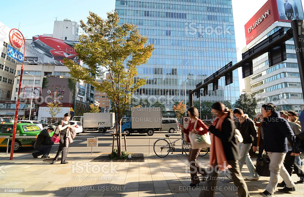 People walk by store building on Omotesando Street stock photo