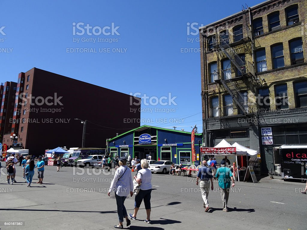 People walk down road toward stadium past food and stock photo