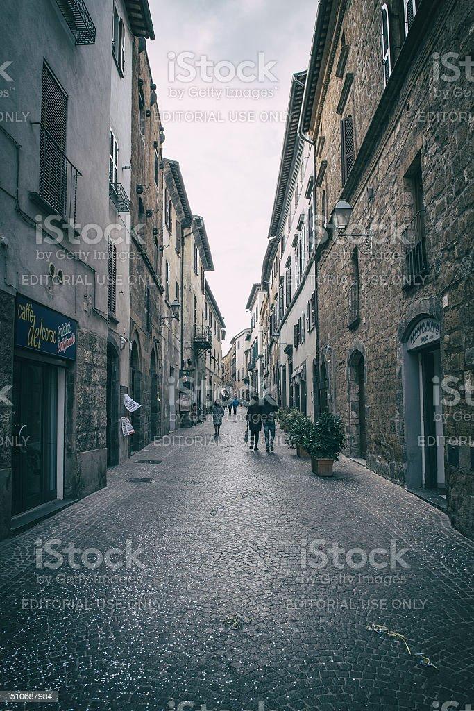 People walk on Orvieto street at dusk stock photo