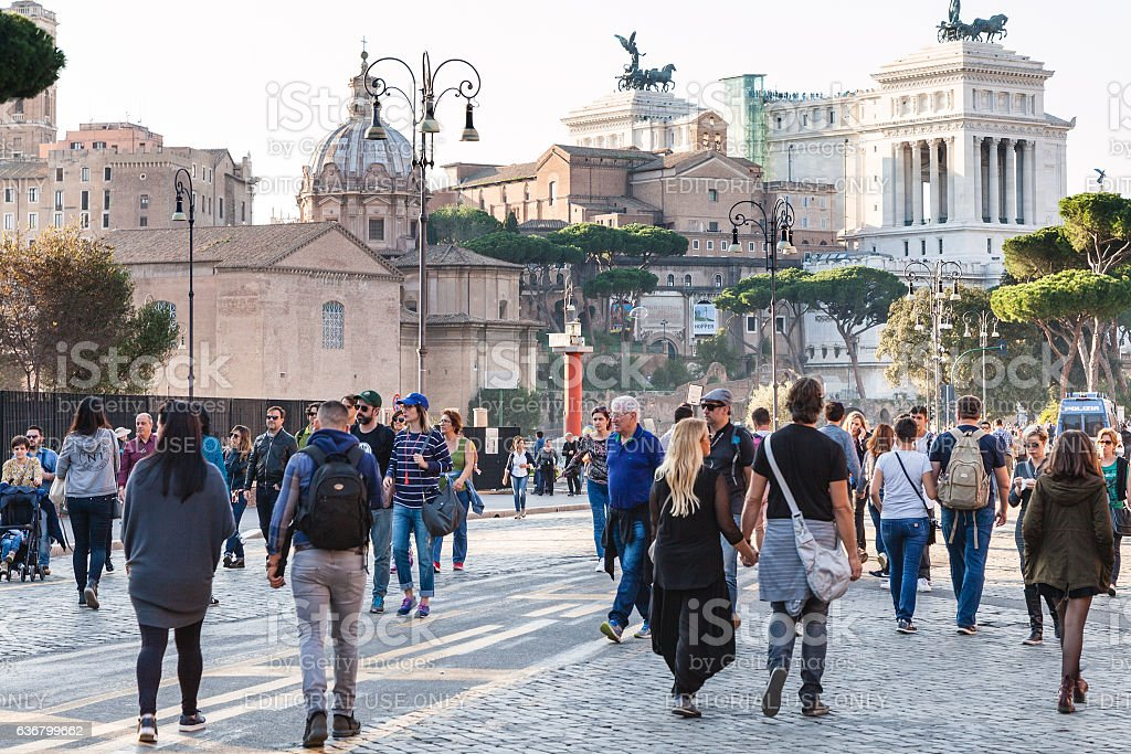people walk on Via dei Fori Imperiali in Rome stock photo