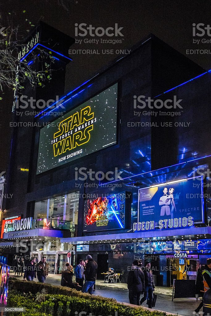 People walk past Leicester Square Odeon cinema, London, at night stock photo