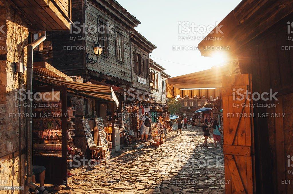 Человек ходить по улицам древних Несебр на закате. стоковое фото
