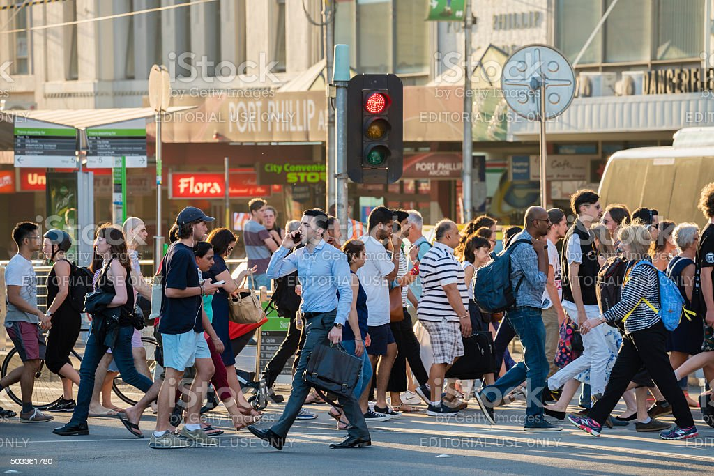 People walking across a busy crosswalk in Melbourne at sunset stock photo