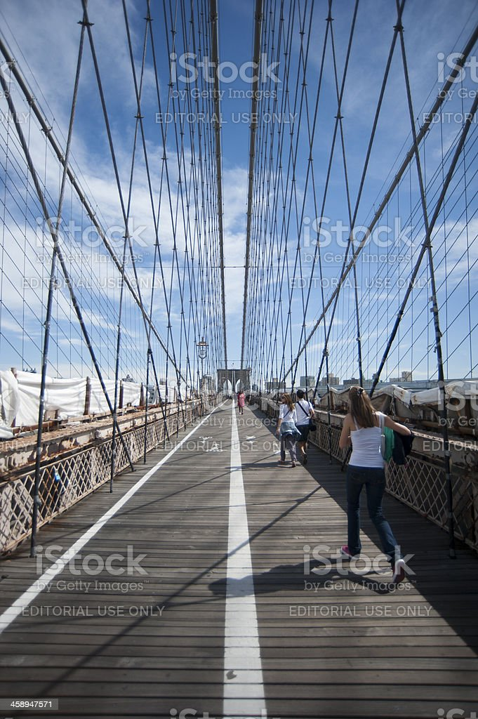 People walking across Brookly Bridge royalty-free stock photo