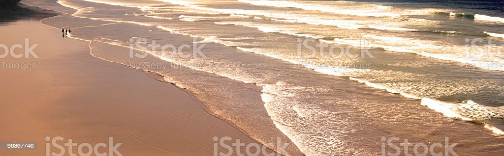 People walking along a beach in the late afternoon stock photo