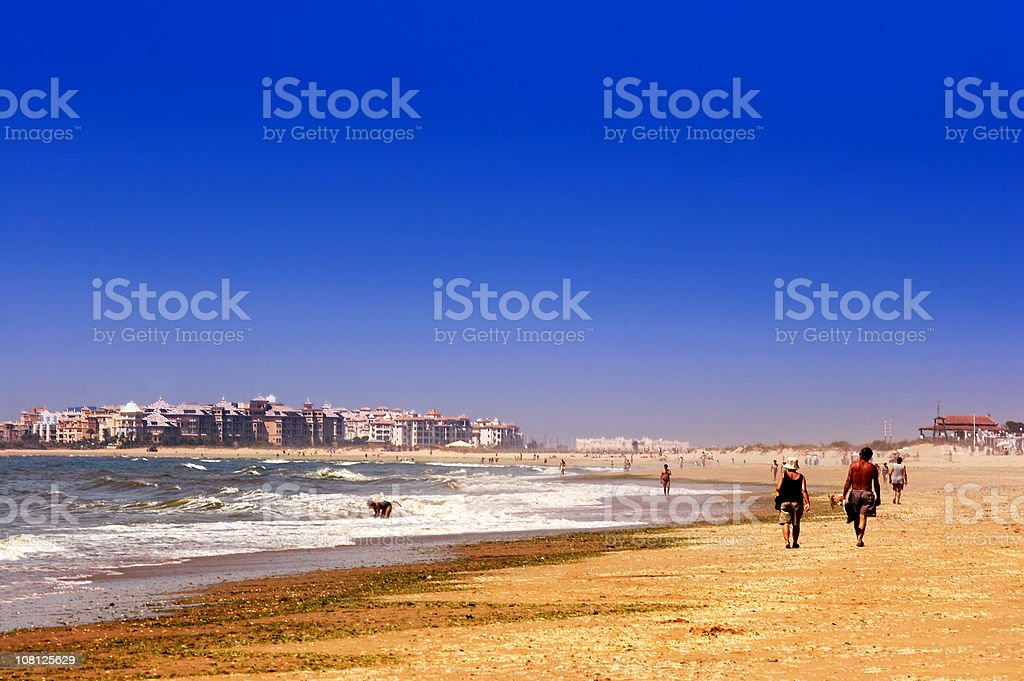 People Walking Along Beach With Blue Sky royalty-free stock photo
