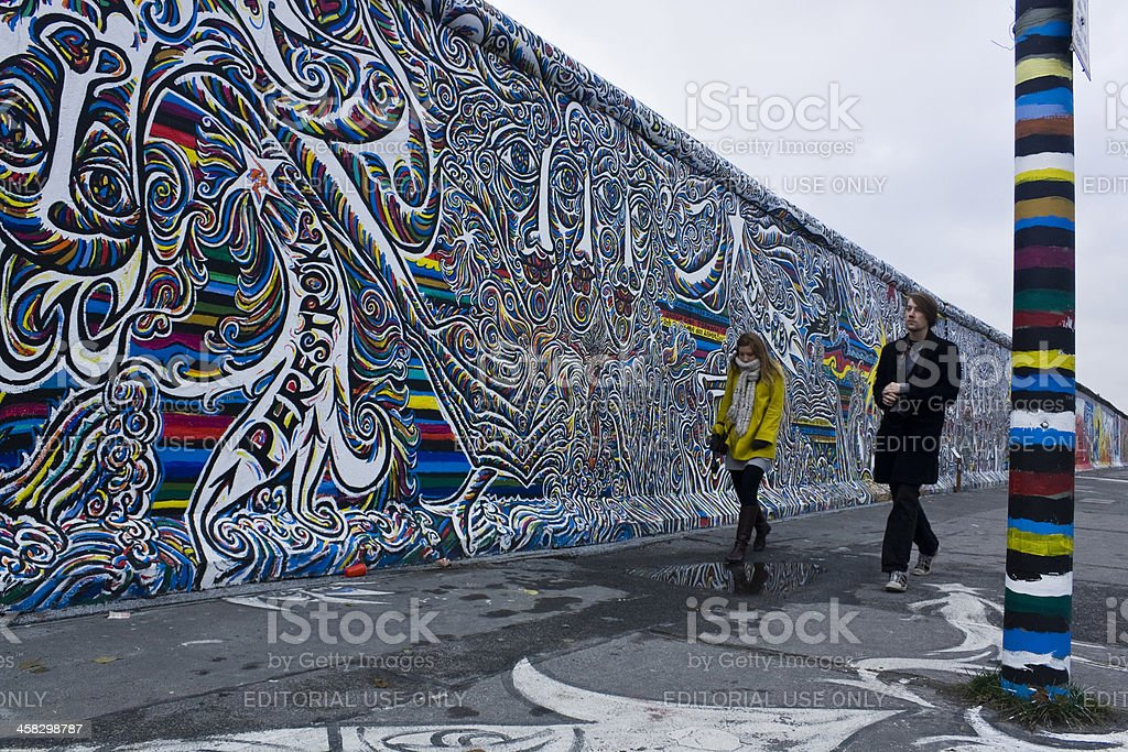 People walking along the wall royalty-free stock photo