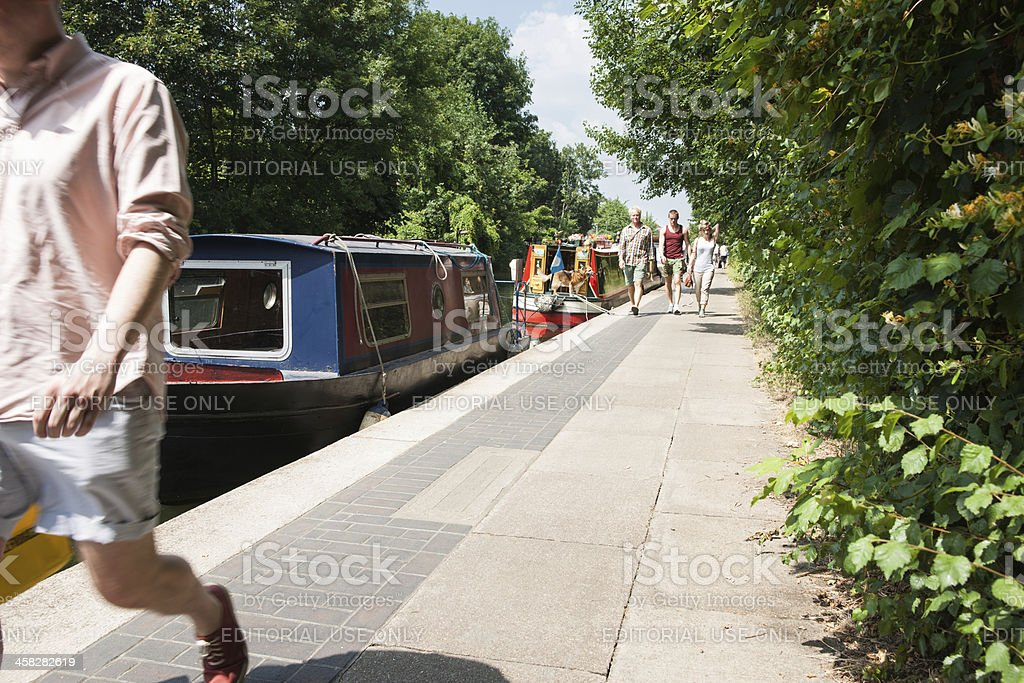 People walking alonside the canal and house boats. stock photo