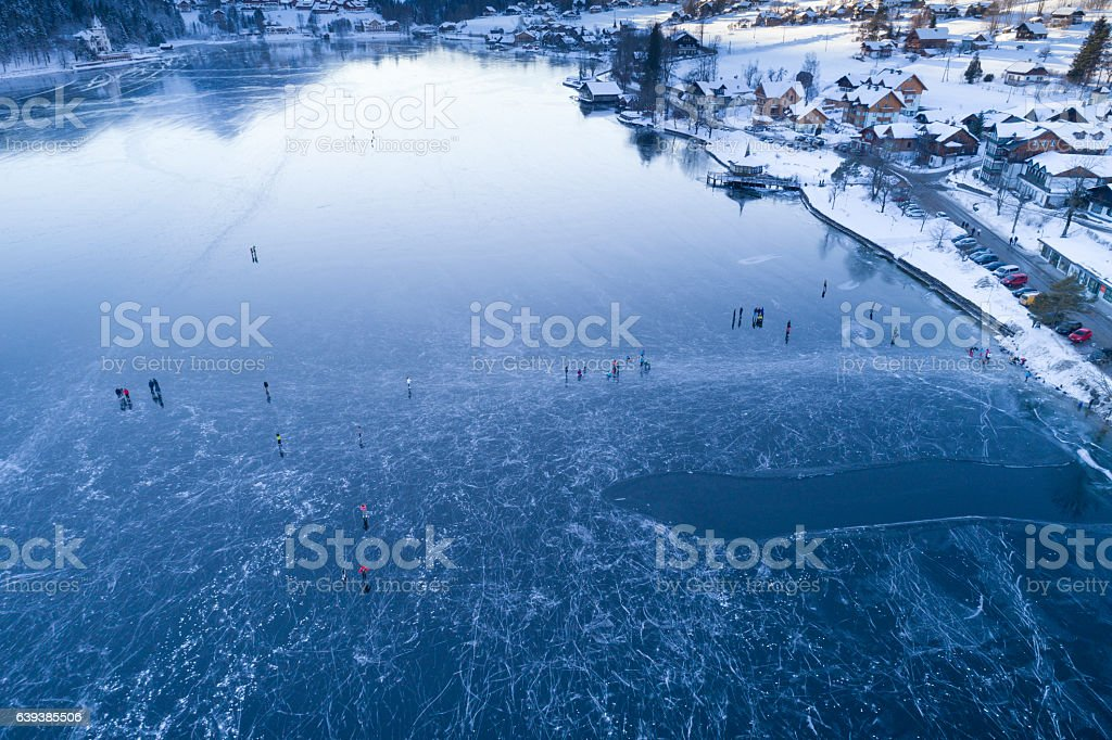 People walking and ice skating on the frozen Lake Grundlsee stock photo