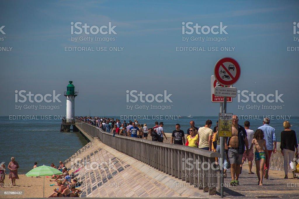 People walking at pier with sealantern at coast calais france stock photo
