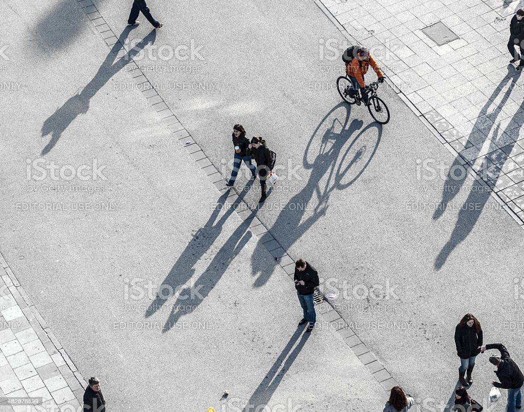 people walking at the street with long shadows stock photo