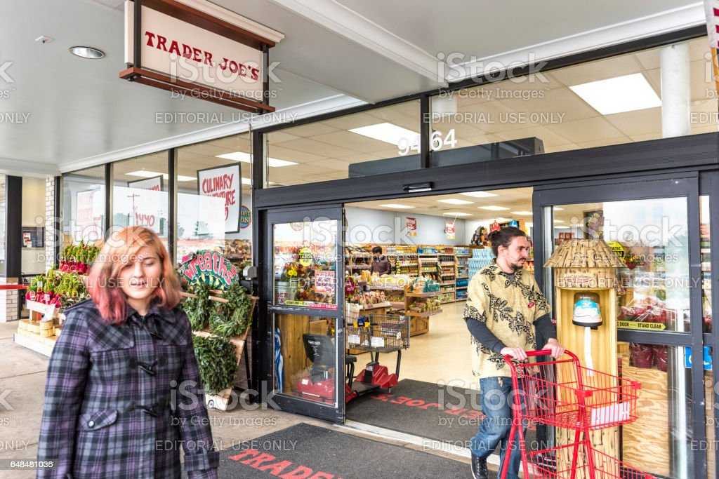 People walking at Trader Joes grocery store by entrance stock photo