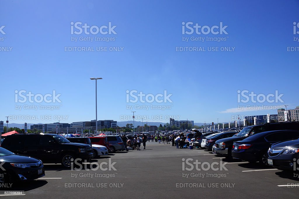 People walking, bbqing, and tailgate in parking lot stock photo