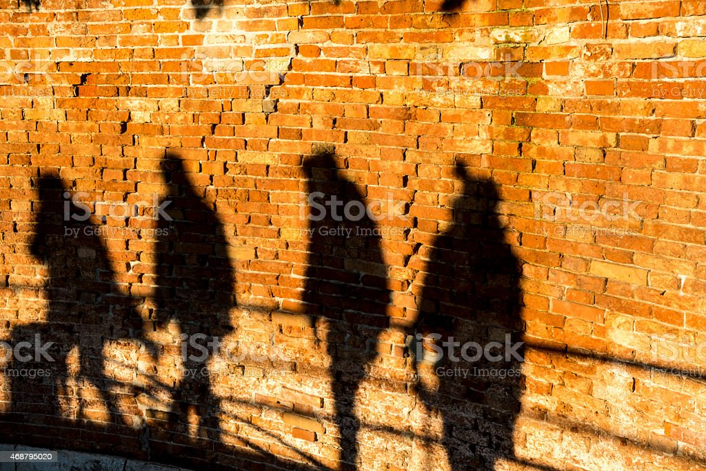 People walking, casting shadows on a wall royalty-free stock photo