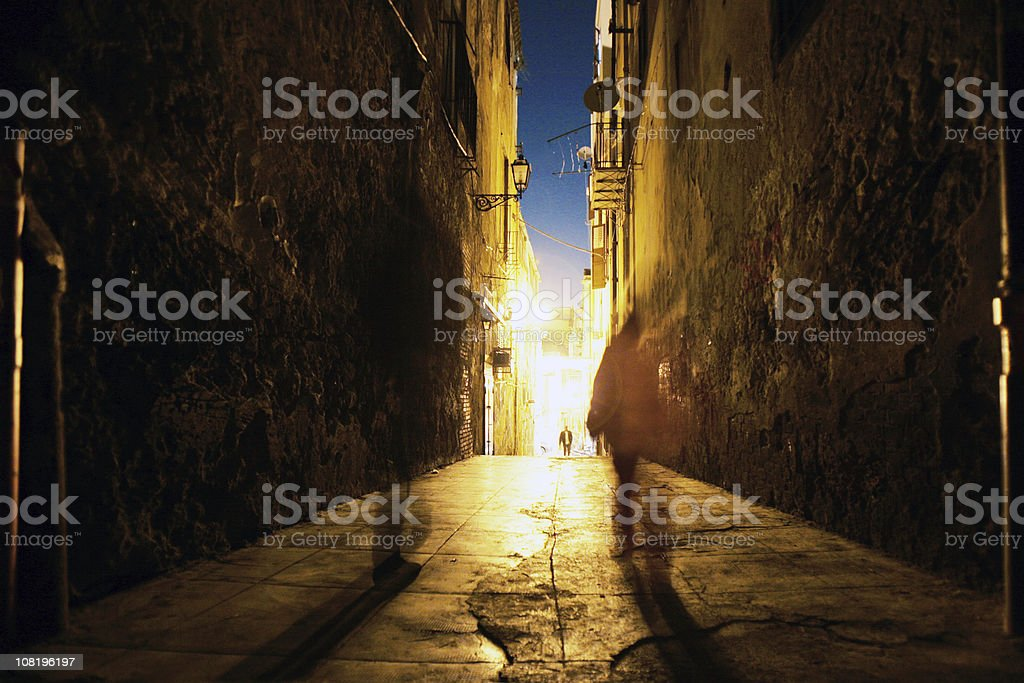 People Walking Down Narrow Street at Night royalty-free stock photo
