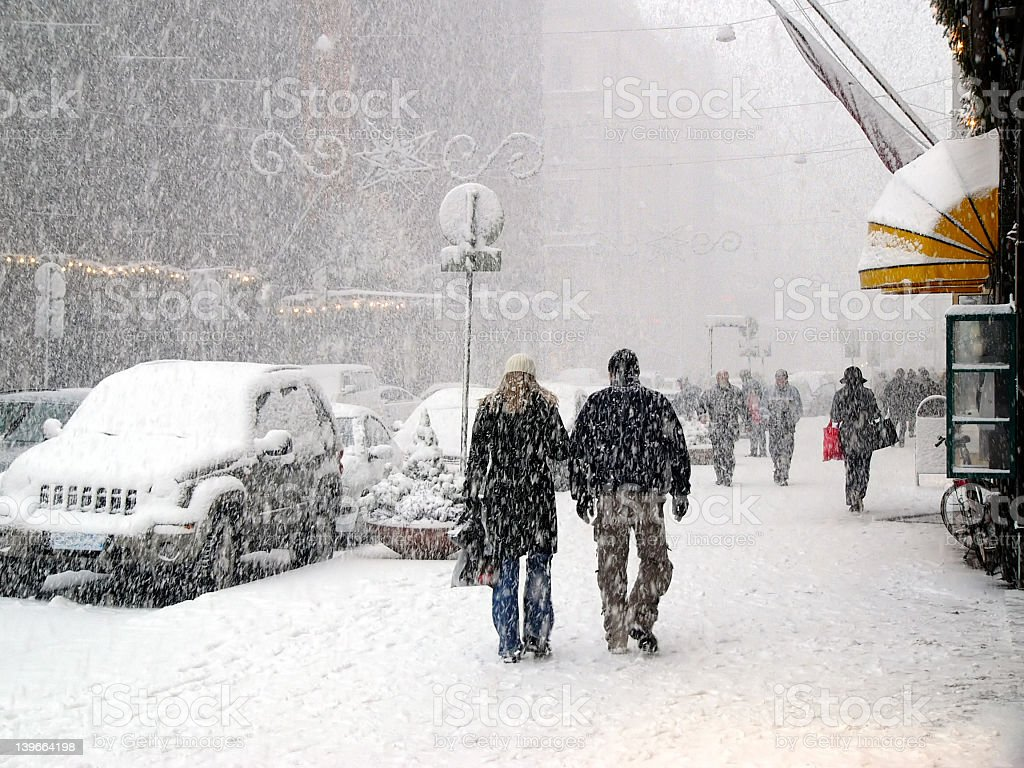 People walking down sidewalks in a snow storm in a city stock photo