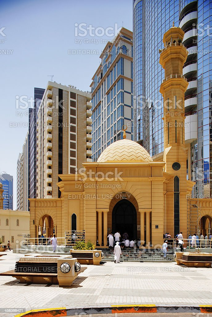 People walking in front of a traditional mosque stock photo