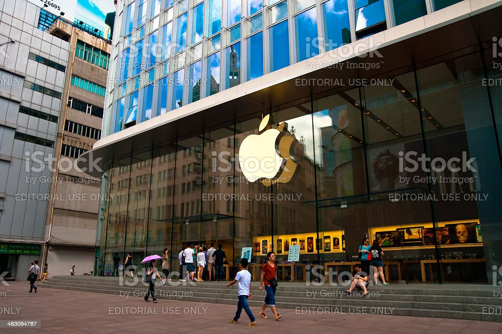 people walking in front of Apple store stock photo
