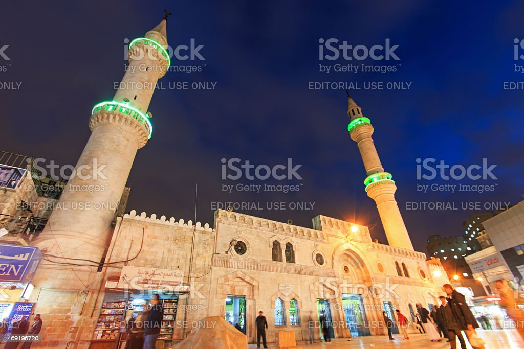 People walking in front of Grand Husseini Mosque in Amman. stock photo