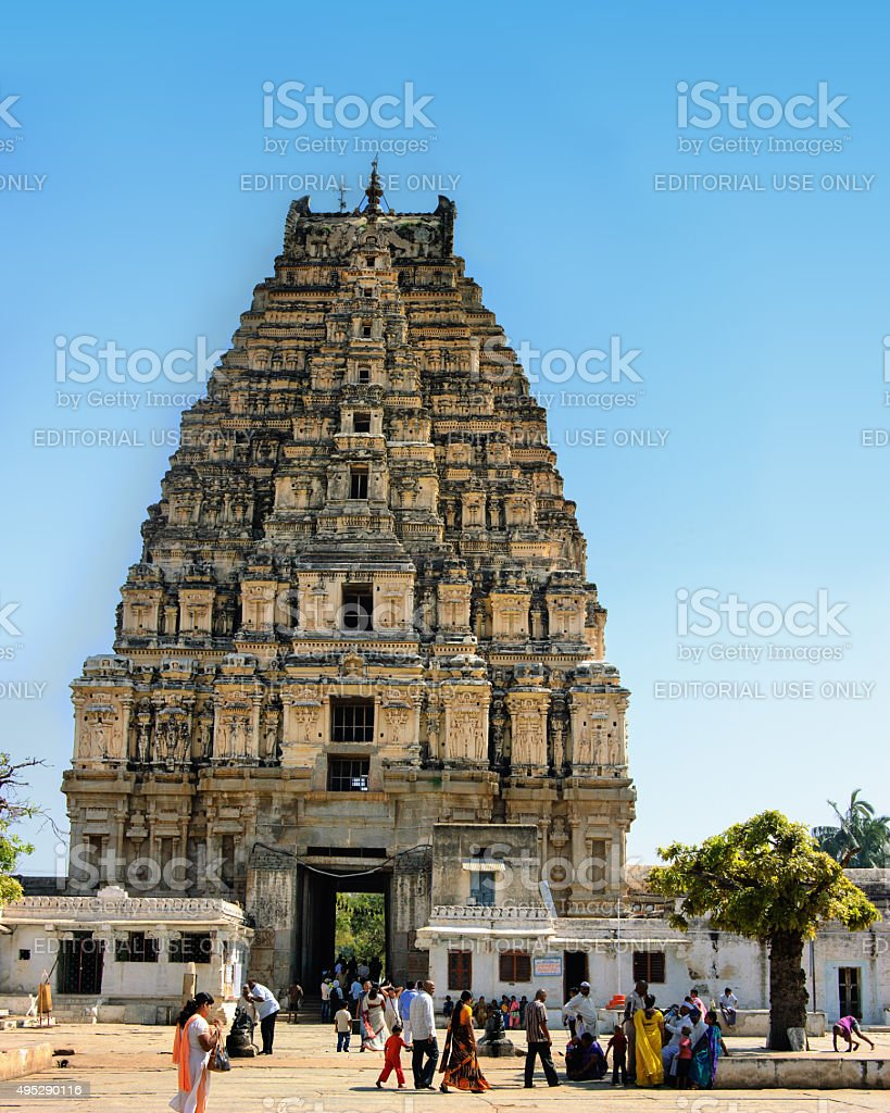 People walking in front of View of Shiva-Virupaksha, Hampi, India. stock photo