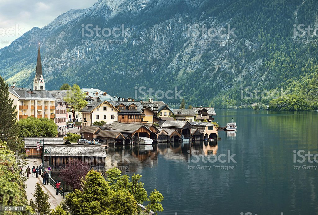 People walking in Hallstatt village on mountains background stock photo