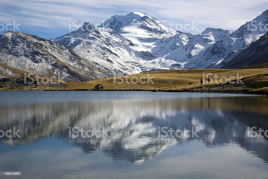 People Walking in Mountain Valley and Field along Lake royalty-free stock photo