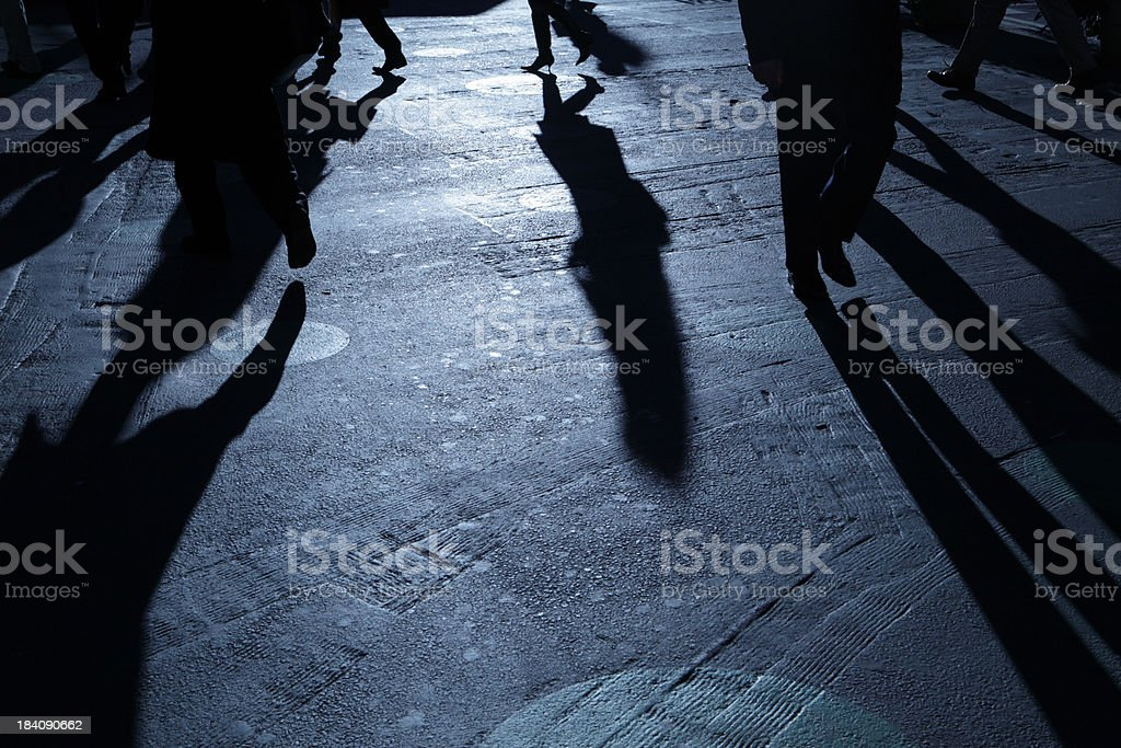 People walking in ominous blue night shadows royalty-free stock photo