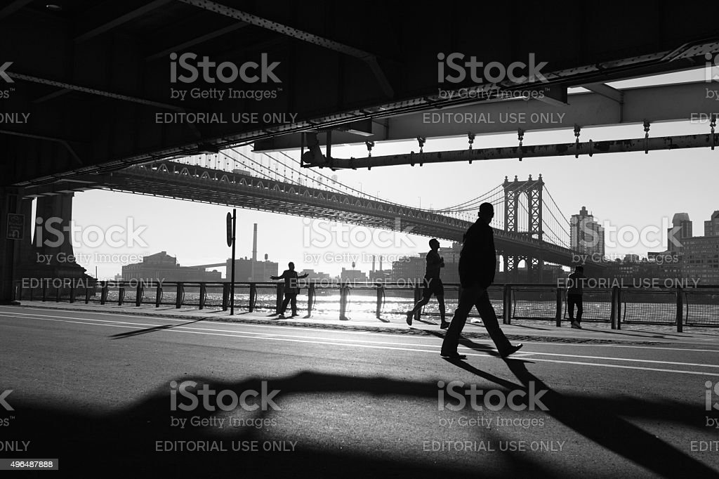 People walking in shadows under the Manhattan Bridge NYC stock photo