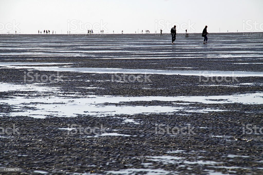 People walking in the distance in a muddy scene in Cuxhaven stock photo