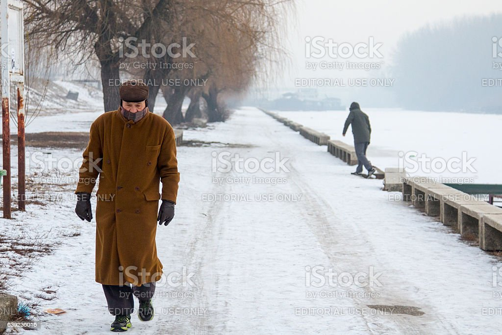 People walking next to frozen river Tamis (a Danube tributary) stock photo
