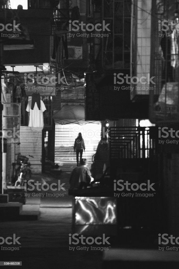 People walking on a dark alley in Zhuhai, China stock photo