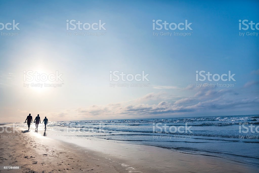 People walking on beach at sunrise stock photo