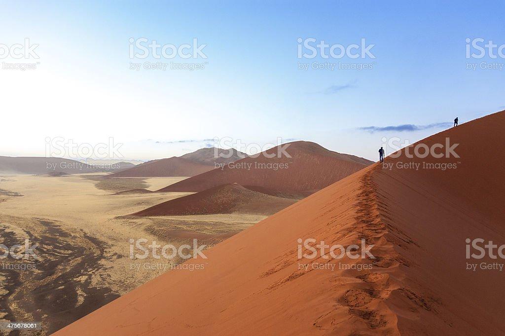 People walking on beautiful sunrise dunes of Namib desert stock photo