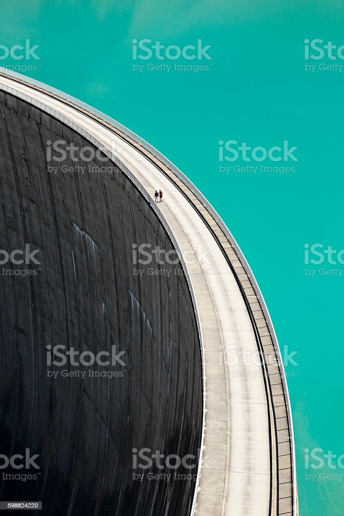 People walking on edge of Stausee Mooserboden Dam, Kaprun, Austria stock photo