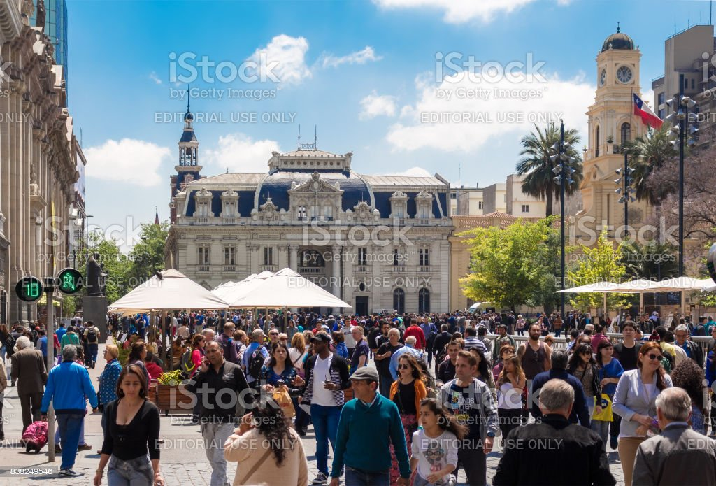 People walking on Plaza de Armas in Santiago, Chile with Central Post Office Building (Correo Central) on the background. stock photo