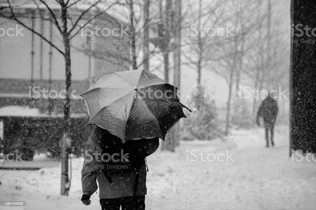 People walking on street in snowstorm stock photo