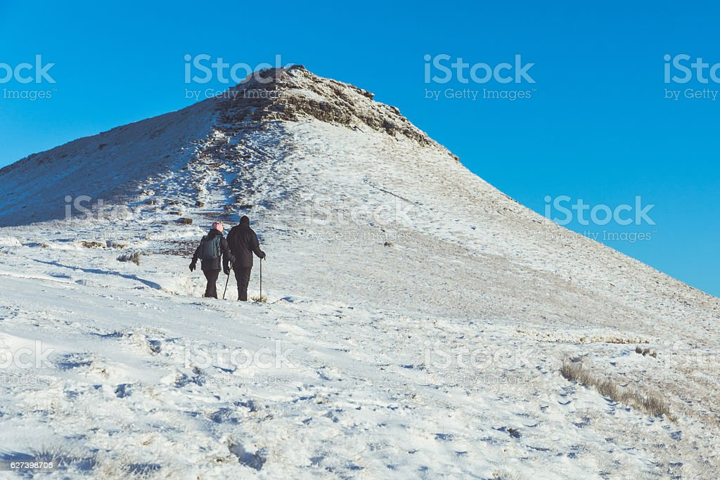 People walking on the snow in a mountain path stock photo
