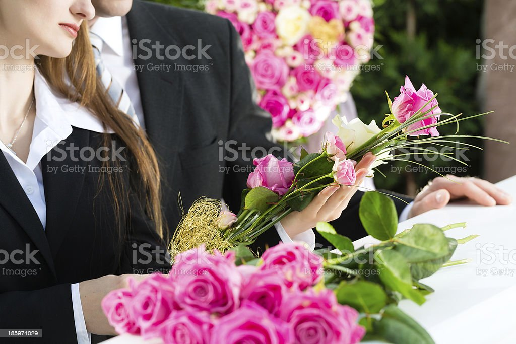 People walking past a coffin with pink flowers at a funeral stock photo
